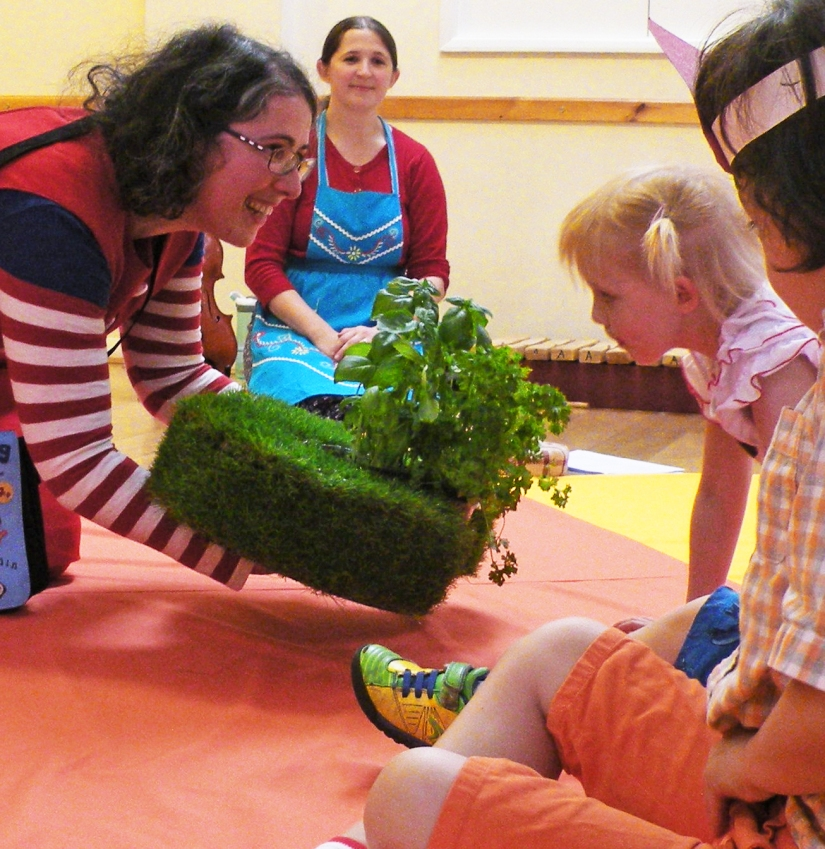 A white woman with curly hair and glasses holds out a prop with live herb plants in to a little girl, who eyes them cautiously