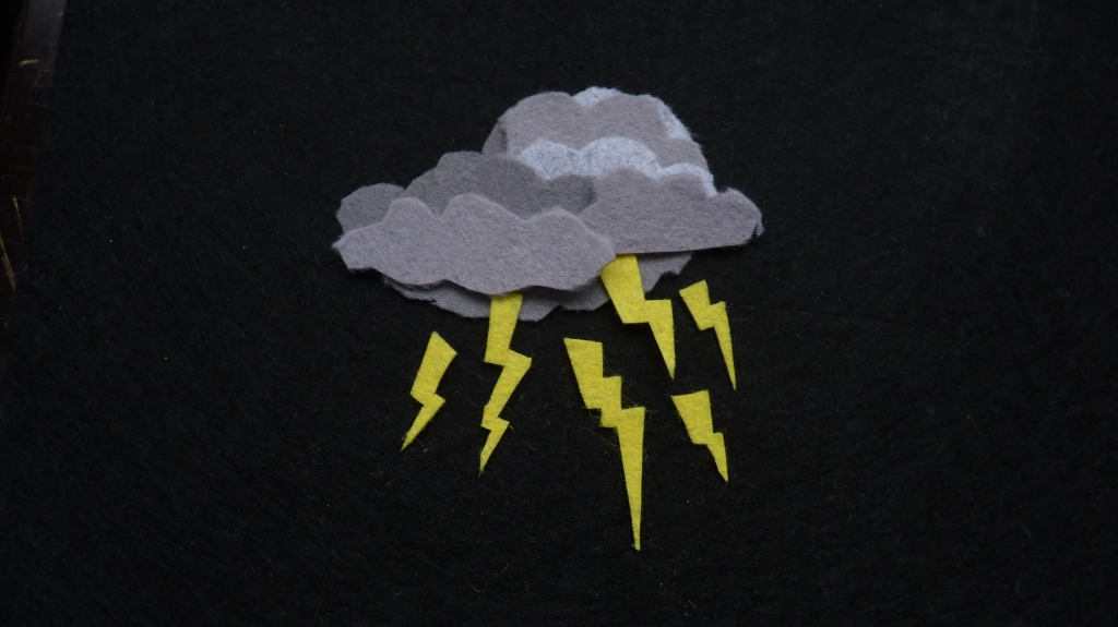 A multi-layered felt thundercloud in lots of shades of grey against a black felt background. The cloud has six jaggedy yellow zigzags of lightning coming out of it in different directions, some smaller, a couple of 'em whoppers. It looks quite scary and a bit angry.